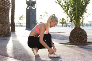 ung passande kvinna som knyter skosnören på sina löparskor utomhus foto