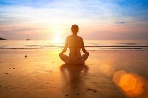 kvinna som utövar yoga på stranden vid solnedgången. foto