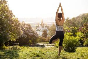 ung kvinna som utövar yoga utomhus foto