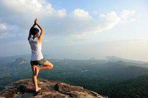 kvinna bergstopp klippa öva yoga foto