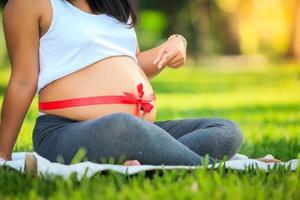 vacker gravid asiatisk kvinna som kopplar av i parken foto