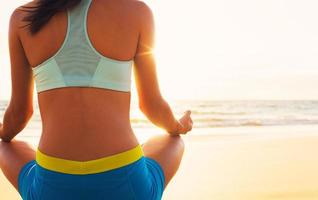 kvinna som utövar yoga på stranden vid solnedgången foto