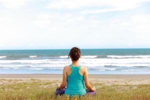 kvinna mediterar framför havet foto