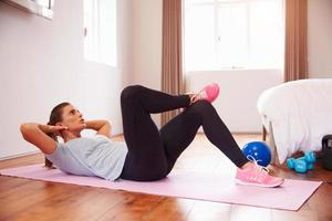 kvinna gör fitnessövningar på matta i sovrummet foto