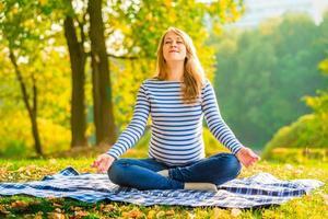 gravid kvinna i lotusställning utför andningsövningar foto
