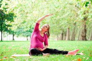 gravid kvinna som spelar yoga på hyde parken, London foto