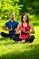 ung man och kvinna som gör yoga på den soliga sommaren foto