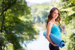 söt kvinna med en yogamatta utomhus. foto