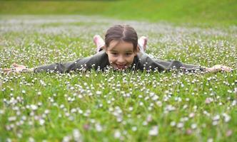 liten flicka som tycker om blommor foto