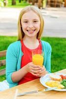 liten flicka njuter av middag. foto