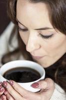 kvinna njuter av färskt kaffe foto