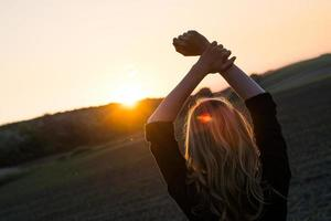 ung kvinna tycker om solstrålar foto