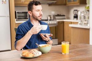 killen njuter av kaffe till frukosten foto