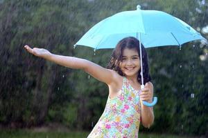 ung flicka njuter av regnet foto
