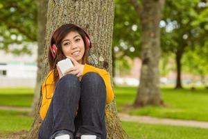 avslappnad kvinna som njuter av musik i parken foto
