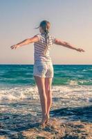 flicka njuter av naturen på stranden foto