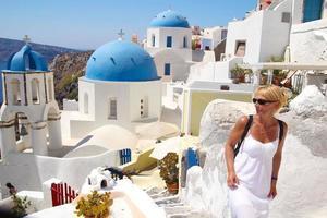 kvinna njuter av utsikt över santorini, Grekland foto