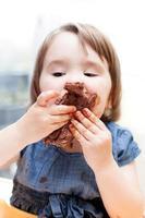liten flicka som tycker om sin födelsedagstårta. foto