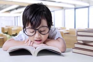 lilla student tycker om att läsa böcker i klassen foto