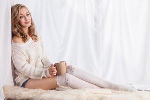 kvinna njuter av kaffe medan du kopplar av hemma foto