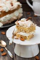 tårta med maräng, vispad grädde och mandlar på träbakgrund foto
