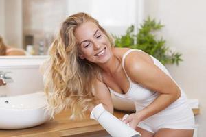 vacker blond kvinna njutning under torkning hår foto