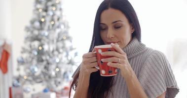 kvinna njuter av en kopp julkaffe