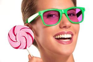 vacker flicka njuta av en stor färgglad godis foto