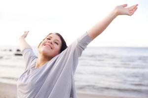 kvinna njuter av frisk luft i havet foto