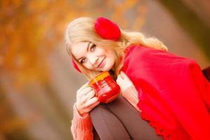 flicka i höst park njuter av varm dryck foto