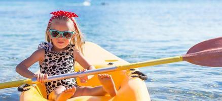 liten söt tjej som tycker om att simma på gul kajak
