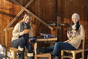 två unga kvinnor tycker om snö för vinterstugan