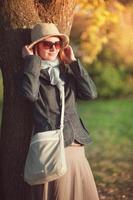 vacker kvinna i hatt och halsduk njuter av solljus foto