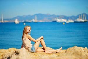 vacker flicka njuter av sin semester vid havet foto