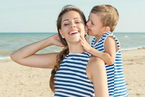 glad vacker mor och son njuter av stranden