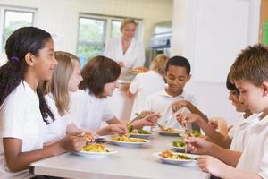 skolbarn njuter av sin lunch i en skolcafeteria foto