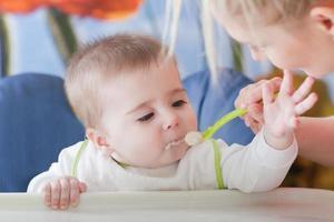 litet barn njuter av sin första smak av mat foto