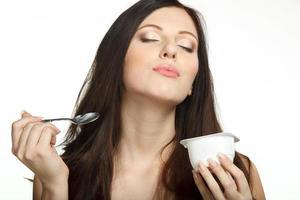 brunhårig ung kvinna som tycker om yoghurt med sked foto