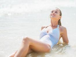 glad ung kvinna som tycker om att lägga i havsvatten foto