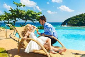 lycklig brud och brudgum njuter av en oändlighet vid poolen vid poolen foto