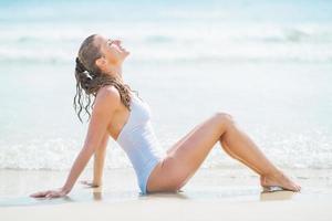 ung kvinna i baddräkt njuter av att sitta vid kusten foto