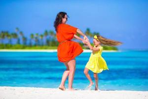 liten bedårande tjej och lycklig mamma tycker om strandsemester foto