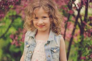 söt barn tjej njuter av våren i mysig trädgård foto