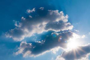 moln på blå himmel med sol
