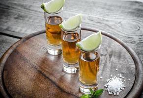 glas tequila på träplattan foto