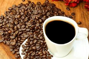 kaffekopp och bönor på en träbakgrund. foto