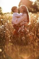 lycklig moderkommunikation med sonen i ett vetefält foto
