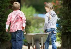 två barn som leker med skottkärra i trädgården foto