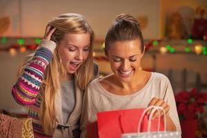 glada två flickvänner som utforskar väskor efter shopping foto