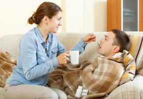 kvinnor som ger tabletter till sin man foto
